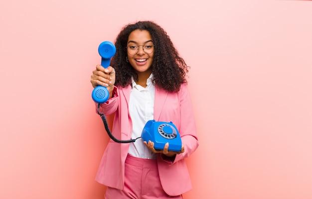 Junge schwarze hübsche frau mit einem weinlese-telefon gegen rosa wand