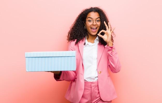 Junge schwarze hübsche frau mit einer geschenkbox gegen rosa wand
