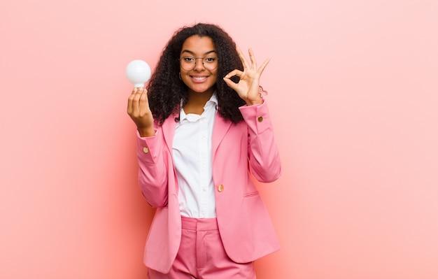Junge schwarze hübsche frau mit einer glühbirne, die eine idee gegen rosa wandhintergrund hat