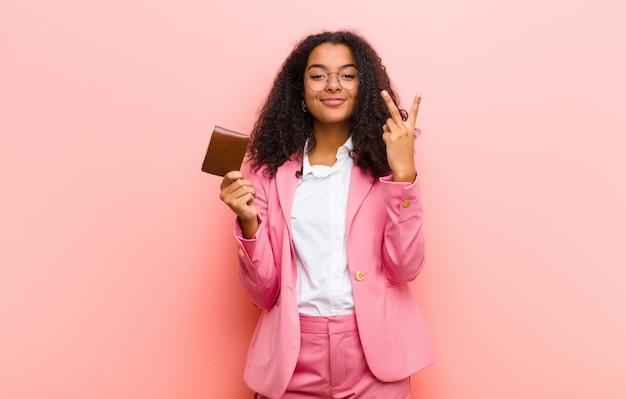 Junge schwarze hübsche geschäftsfrau mit einer brieftasche gegen rosa wandhintergrund