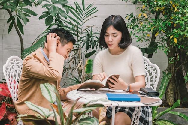 Junge schwester, die hausaufgaben zur jüngeren bruderaufmerksamkeit unterrichtet, um zu hören