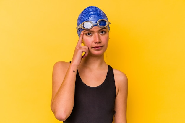 Junge schwimmer venezolanische frau lokalisiert auf gelbe wand, die tempel mit dem finger zeigt, denkend, konzentrierte sich auf eine aufgabe