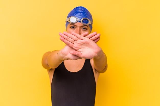 Junge schwimmer venezolanische frau lokalisiert auf gelber wand, die eine verweigerungsgeste tut