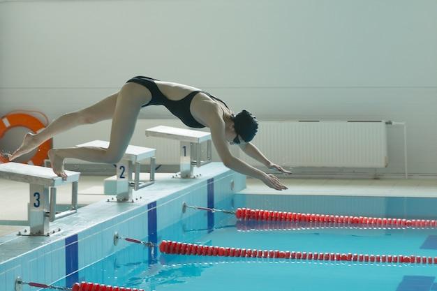 Junge schwimmerin, die ins hallenbad springen und eintauchen. sportliche frau.