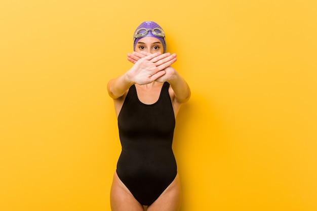 Junge schwimmerkaukasierin, die eine verweigerungsgeste tut