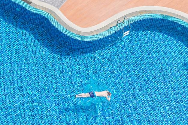 Junge schwimmt im außenpool von der draufsicht