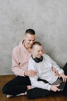 Junge schwule paare, die mit laptop auf dem boden sitzen, mit kopfhörern zusammen musik hören, sich umarmen oder umarmen.