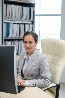 Junge sekretärin tippt vor computermonitor