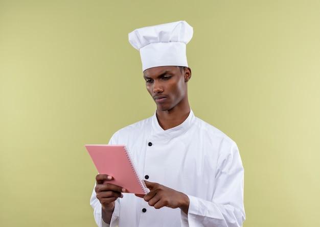 Junge selbstbewusste afroamerikanische köchin in der kochuniform betrachtet notizbuch lokalisiert auf grünem hintergrund mit kopienraum