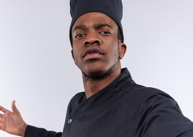 Junge selbstbewusste afroamerikanische köchin in der kochuniform gibt vor, kamera lokalisiert auf weißem hintergrund mit kopienraum zu halten