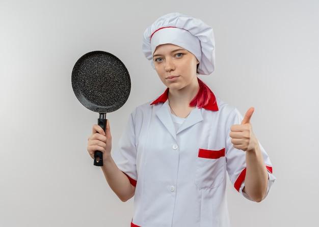 Junge selbstbewusste blonde köchin in kochuniform hält bratpfanne und daumen lokalisiert auf weißer wand