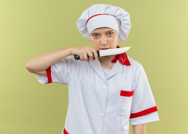 Junge selbstbewusste blonde köchin in kochuniform hält messer und sieht isoliert auf grüner wand aus