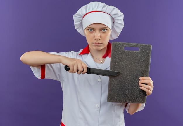 Junge selbstbewusste blonde köchin in kochuniform hält schneidebrett abd punkte mit messer lokalisiert auf violetter wand