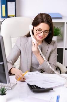 Junge selbstbewusste brünette geschäftsfrau in der abendgarderobe, die finanzdokumente beim beraten des kunden am telefon durchschaut