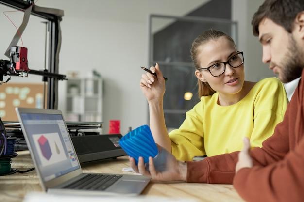 Junge selbstbewusste designerin, die mit ihrem kollegen mit blauem plastikgegenstand spricht, der auf 3d druckmaschine gedruckt wird
