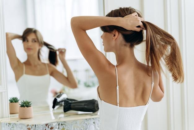 Junge selbstbewusste frau, die weiße hauskleidung trägt und ihr spiegelbild betrachtet, während sie am spiegel sitzt und lange gesunde brünette haare bürstet. tausendjähriges weibchen, das morgens pferdeschwanz macht