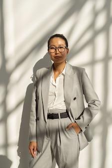 Junge selbstbewusste geschäftsfrau asiatischer abstammung, die an der weißen wand steht