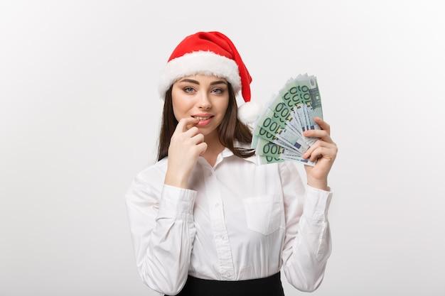 Junge selbstbewusste geschäftsfrau des weihnachts- und finanzkonzepts, die geld vor ihr mit glücklichem gesicht zeigt