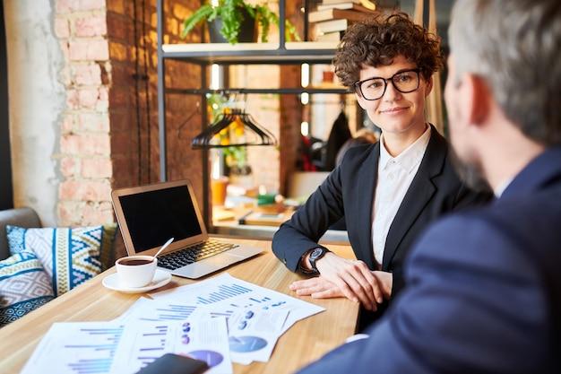 Junge selbstbewusste geschäftsfrau, die kollegen ansieht, während sie seine arbeitsideen beim start-up-treffen hört