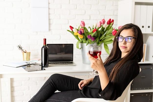 Junge selbstbewusste geschäftsfrau, die wein trinkt und frühlingsferien im büro feiert