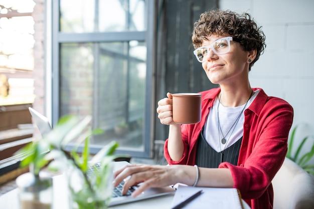 Junge selbstbewusste geschäftsfrau mit becher des getränks, die am tisch vor laptop, vernetzung oder planungsarbeit sitzt