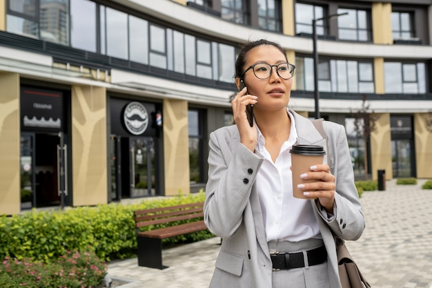 Junge selbstbewusste geschäftsfrau mit smartphone nach gehör