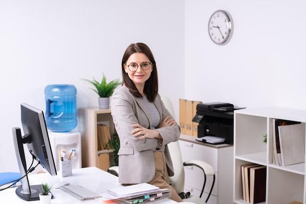 Junge selbstbewusste geschäftsfrau mit verschränkten armen auf der brust, die auf schreibtisch mit dokumenten und computermonitor im büro sitzt