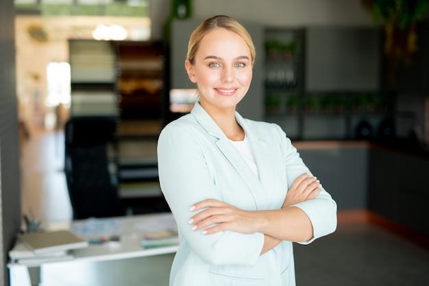 Junge selbstbewusste geschäftsführerin in der abendgarderobe, die sie beim stehen in ihrem büro ansieht