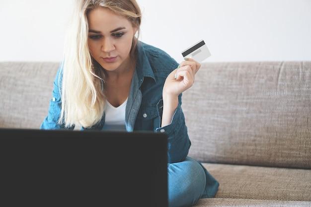 Junge selbstbewusste hübsche frau, die zu hause mit laptop und kreditkarte arbeitet