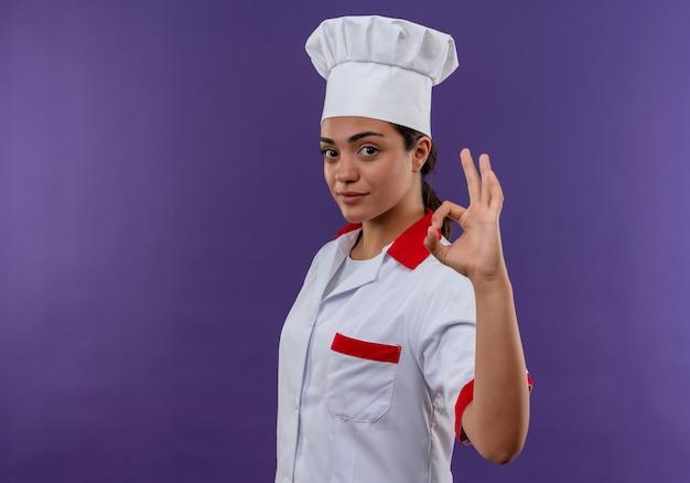 Junge selbstbewusste kaukasische köchin in der kochuniform steht seitlich und gestikuliert ok handzeichen lokalisiert auf violetter wand mit kopienraum