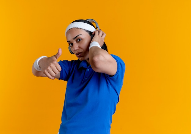 Junge selbstbewusste kaukasische sportliche frau, die stirnband und armbänder auf kopfhörern trägt, daumen hoch auf orange mit kopienraum