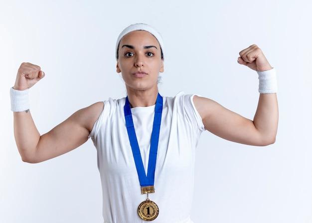 Junge selbstbewusste kaukasische sportliche frau, die stirnband und armbänder mit goldmedaille spannt bizeps lokalisiert auf weißem raum mit kopienraum