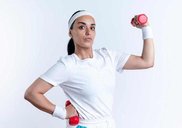 Junge selbstbewusste kaukasische sportliche frau, die stirnband und armbänder spannt, spannt bizeps, der hanteln lokalisiert auf weißem raum mit kopienraum hält