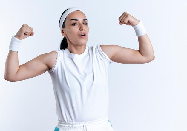 Junge selbstbewusste kaukasische sportliche frau, die stirnband und armbänder spannt, spannt bizeps lokalisiert auf weißem raum mit kopienraum