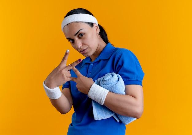 Junge selbstbewusste kaukasische sportliche frau, die stirnband und armbänder trägt, gestikuliert siegeshandzeichen, das handtuch mit arm auf orange mit kopienraum hält