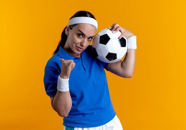 Junge selbstbewusste kaukasische sportliche frau, die stirnband und armbänder trägt, hält ball, der zurück zeigt