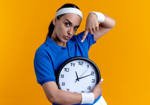 Junge selbstbewusste kaukasische sportliche frau, die stirnband und armbänder trägt, hält und zeigt auf uhr auf orange mit kopienraum