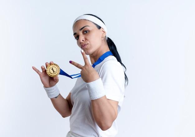 Junge selbstbewusste kaukasische sportliche frau, die stirnband und armbänder trägt, steht seitlich und hält goldmedaille und gestikulierendes siegeshandzeichen lokalisiert auf weißem raum mit kopienraum