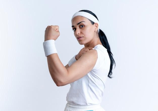Junge selbstbewusste kaukasische sportliche frau, die stirnband und armbänder trägt, steht seitlich und spannt bizeps lokalisiert auf weißem raum mit kopienraum