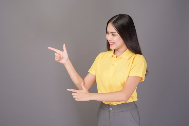 Junge selbstbewusste schöne frau, die gelbes hemd trägt, ist auf grauem studio