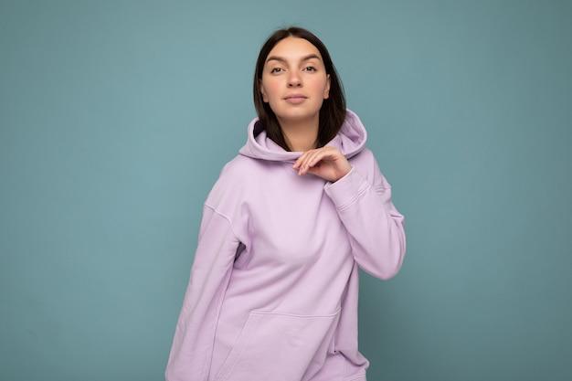 Junge selbstbewusste sexy schöne brünette frau mit aufrichtigen emotionen isoliert auf der hintergrundwand mit kopierraum, die einen lässigen, stylischen lila hoodie mit blick auf die kamera trägt