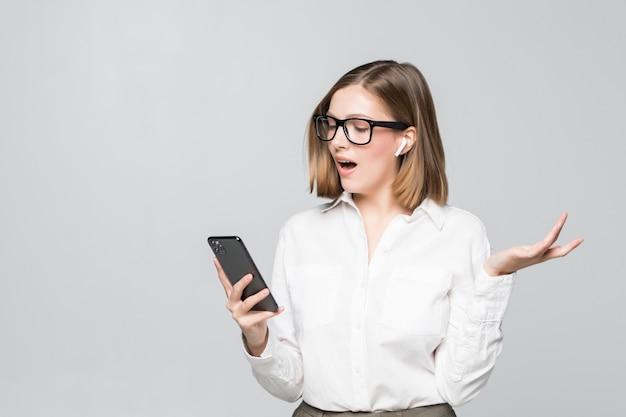 Junge, selbstbewusste und schöne geschäftsfrau, die über drahtloses airpod-headset spricht, das telefon lokalisiert auf weiß hält