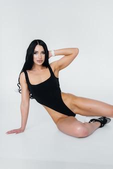 Junge sexy brünette in einem schwarzen body auf weißem hintergrund. die perfekte sportliche figur.