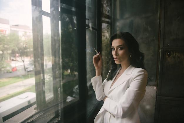 Junge sexy brunettefrau in der klage, die am fenster eine zigarette zuhause raucht