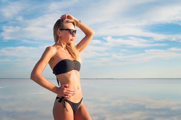 Junge sexy dame mit dem schwarzen badeanzug im urlaub. model posiert in der natur. mädchen, das in die ferne im hintergrundwasser mit reflexionen des bewölkten himmels schaut
