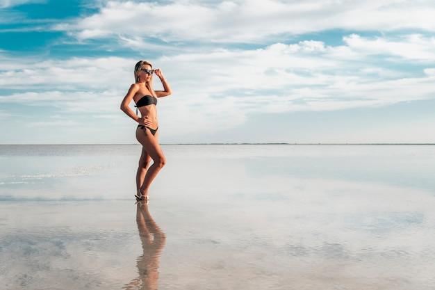 Junge sexy dame mit dem schwarzen badeanzug im urlaub. model posiert in der natur. schönes freies sexy mädchen, das im hintergrundwasser mit bewölkten himmelreflexionen in die ferne schaut