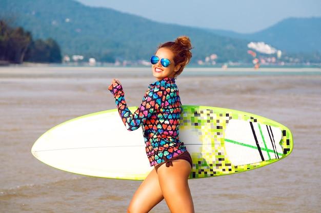 Junge sexy fit glückliche frau, die mit surfbrett am kalifornischen strand läuft