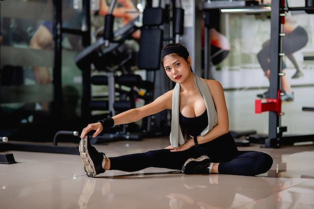 Junge sexy frau des porträts, die sportkleidung und smartwatch trägt, die auf dem boden sitzt und ihre beinmuskeln vor dem training im fitnessstudio streckt,