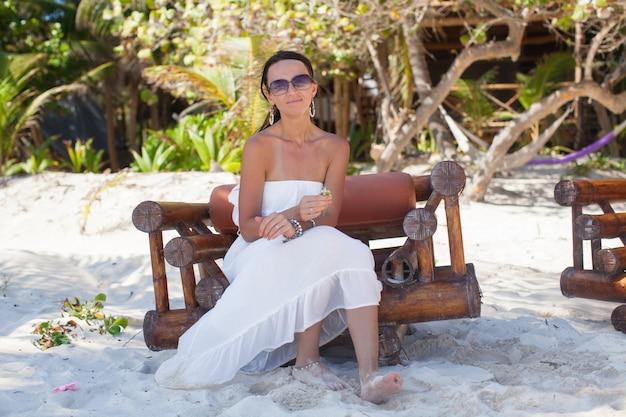 Junge sexy frau, die auf holzstuhl im exotischen tropischen erholungsort sitzt
