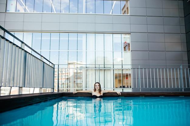 Junge sexy frau, die im wasser an einem pool im sonnigen heißen tag entspannt